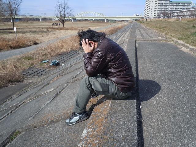 川辺で悩む男性